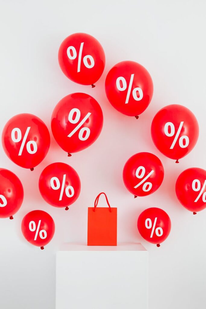 a red paper bag in the middle of red balloons with percentage symbols